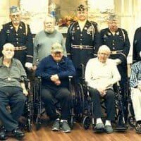 Colonial Courtyard at Clearfield residents who are veterans, front row, from left to right: Bill Graham, George Anderson, Vince Ballaratto, William Owens, Andrew Tocimak, and Richard Passmore. Resident veteran Edward Solensky is standing in the center among Veterans Honor Guard of the Clearfield American Legion Post 6 and Clearfield VFW Post 1785.