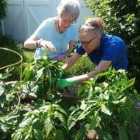 Resident in Memory Care gardens with the help of a caregiver