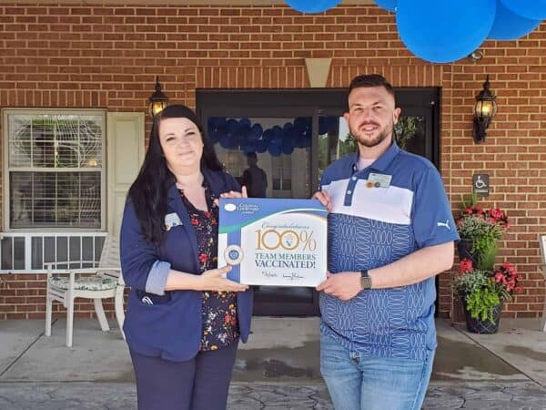 Photo Cutline information: IntegraCare Director of Operations Western Region Belinda McQuaide presents a certificate to Colonial Courtyard at Bedford Executive Operations Officer Brian Hall. Colonial Courtyard at Bedford attained 100% COVID-19 vaccinations among team members.