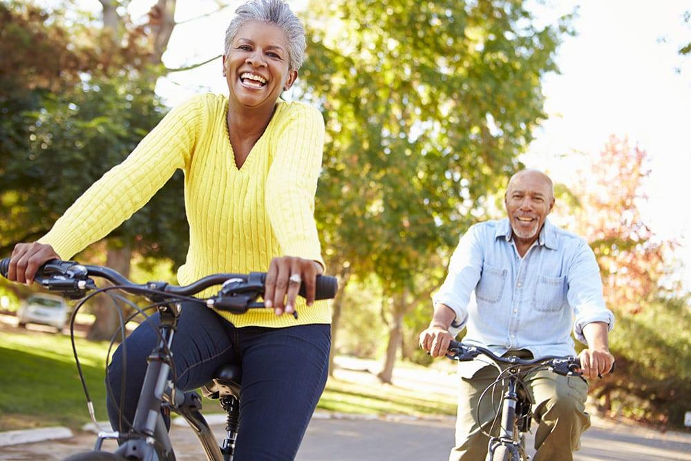 Senior couple riding bikes, happy outside